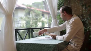 Man reading book, drinking coffee, while sitting on balcony