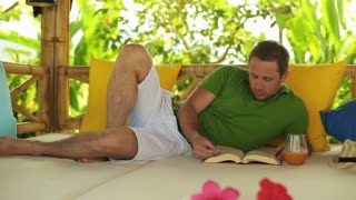 Man reading book in exotic garden