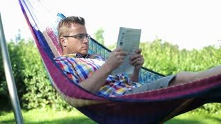 man reading newspaper and lying in the hammock