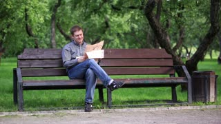 Man reads a newspaper on a bench in the park 1