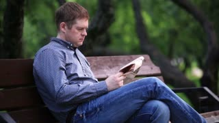 Man reads a newspaper on a bench in the park 2