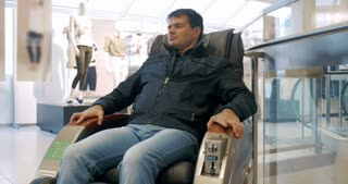 Man relaxing in comfortable fee-paying massage arm-chair. Easy rest after shopping in trade centre