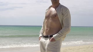Man relaxing on the beach, slow motion shot at 60fps