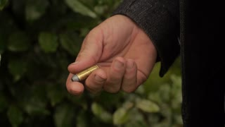 Man Rolling Gold Bullet In Hand