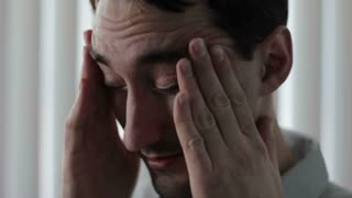 Man rubbing his temples with a headache