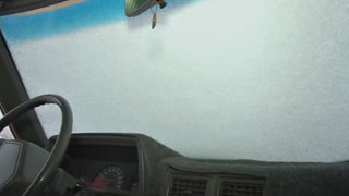 Man Scraping Snow and Ice Off Windshield