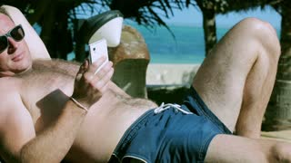Man sending message and lying on sunbed, steadycam shot