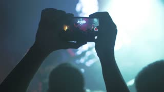 Man shooting video with smartphone in the club at the concert, 4k
