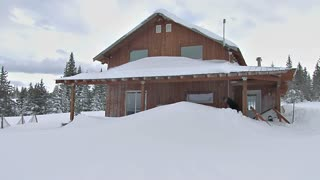 Man Shoveling Snow Drift off Snow Covered House After Blizzard