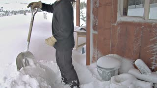 Man Shoveling Snow Off Deck of House Covered in Snow After Blizzard