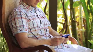 Man sitting and texting on cellphone in the garden