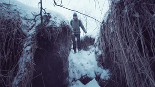 Man sitting in hay in winter and catching a signal to find a way