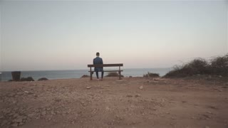 Man Sitting On A Bench Facing The Sea