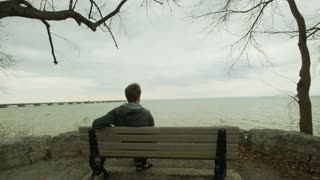 Man Sitting on Bench By Lake