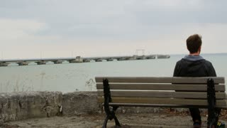 Man Sitting On Bench Overlooking Water