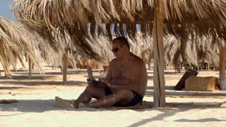 Man sitting on the beach under straw umbrella and using laptop