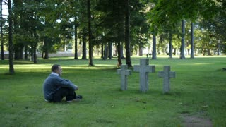 Man sitting on the grass in a cemetery or park mourning in front of three simple stone crosses