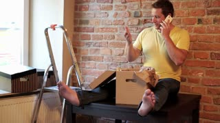 man sitting on the table in his new flat and talking on the phone