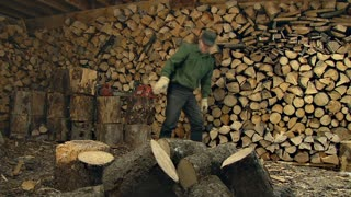 Man Splittig Firewood in Woodshed