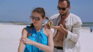 Man spread sunblock on his girlfriend