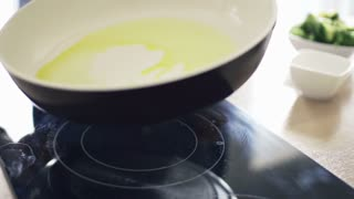 Man spreading olive oil on pan over induction hob in kitchen, slow motion shot at 240fps