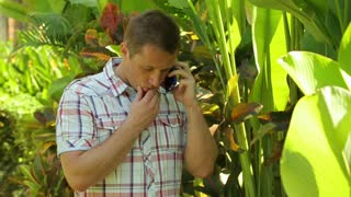 Man standing with cellphone in the garden and getting bad news