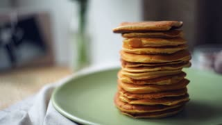 Man take one pancake from stack of pancakes. Dessert food for morning breakfast. Sweet pancake breakfast. Stack of american pancakes on green plate. Freshly baked dessert food