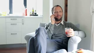 Man talking on cellphone and drinking juice at home