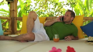 Man talking on cellphone in the garden and lying on bed