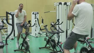 Man talking on cellphone while riding stationary bicycle in health club