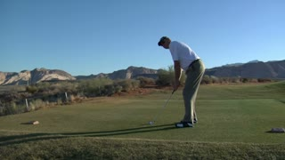 Man Tees Off With Iron On Desert Golf Course
