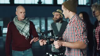 Man testing handheld camera gyro stabilizin gimbal, stretching arms with device and following the moves of stage director