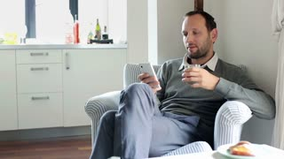 Man texting, using smartphone and drinking juice at home