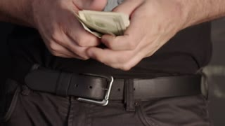 Man tucks money into jeans pocket
