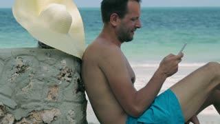 Man using cellphone on the beach, steadycam shot