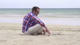 Man using chatting with laptop on the beach, slow motion shot at 60fps