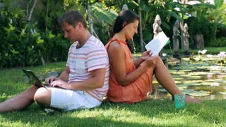 Man using laptop and woman reading book in exotic garden