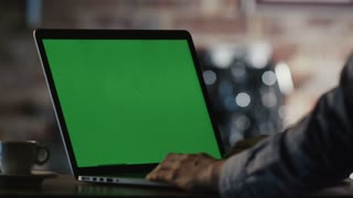 Man using Laptop with Green Screen in Cafe.