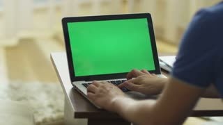 Man Using Laptop with Green Screen in Living Room.