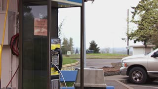 Man Using Public Payphone
