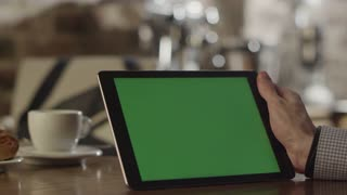 Man using Tablet in Coffee Shop. Tablet with Green Screen.