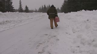 Man Walking Down Road Looking For Gas in Snowstorm