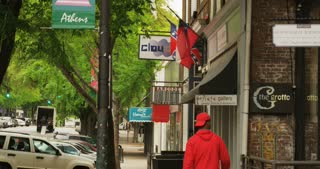 Man Walking on Sidewalk Under Georgia Flags