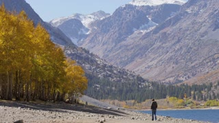 man walks down river bed with distant mountains