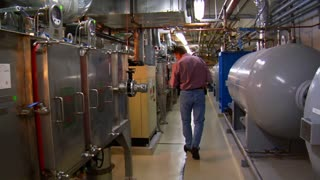 Man Walks Through Complex Machine Room