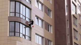 Man washes the windows of office building 1