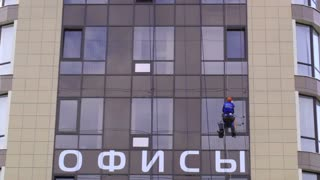 Man washes the windows of office building 2