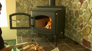 Man With A Baseball Cap  Builds Fire In Wood Stove