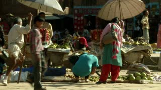 Man with Crutch Moves Through Market in Nepal