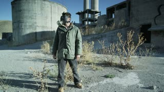man with gas mask surveying abandoned power plant
